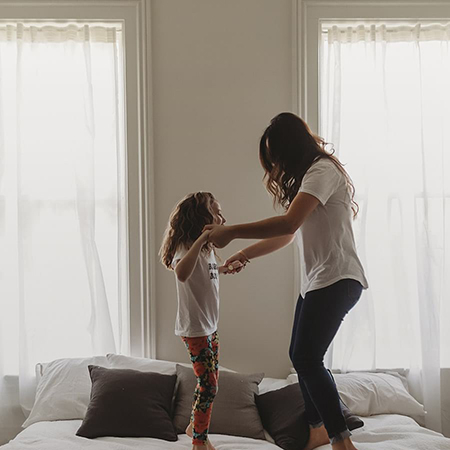 A woman jumping on a bed with her daughter
